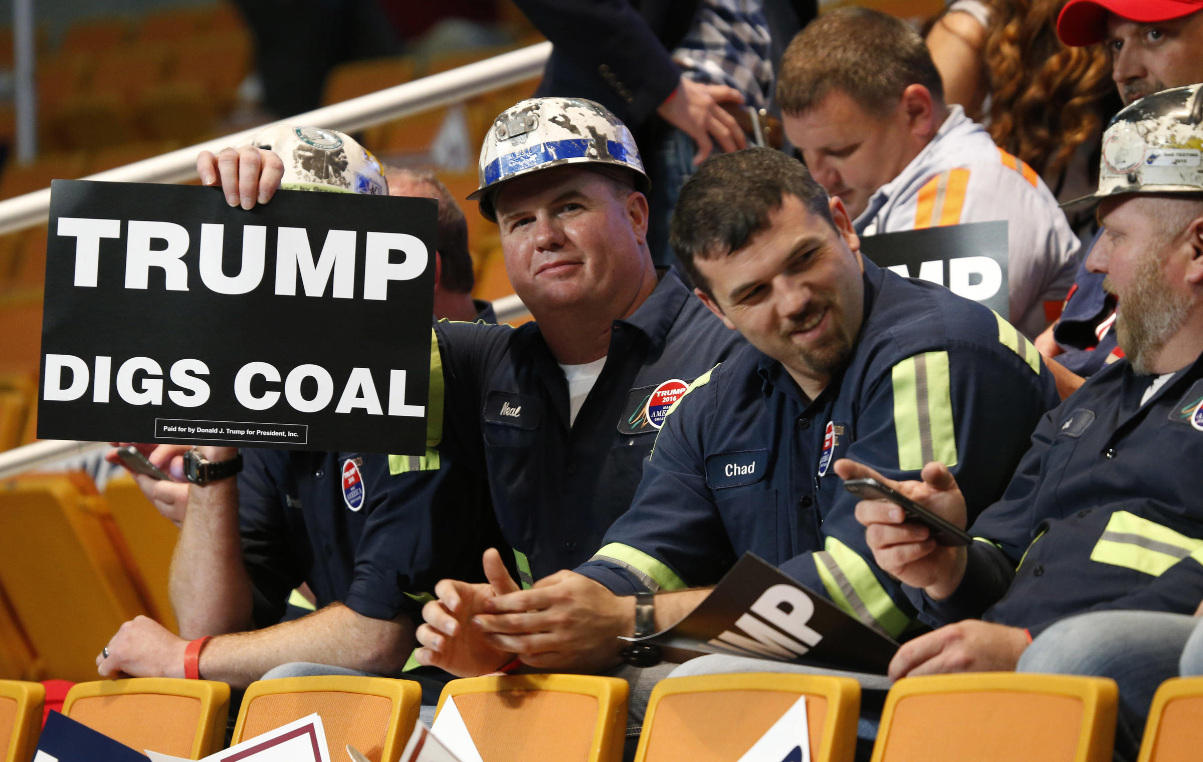A group of coal miners hold Trump signs as they wait for a rally with Republican presidential candidate Donald Trump, Thursday, May 5, 2016, in Charleston, W.Va. (AP Photo/Steve Helber)